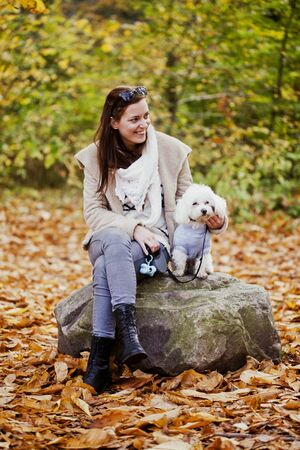 knee boots: Happy woman with Bichon Frise sitting on rock in forest LANG_EVOIMAGES