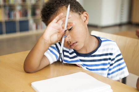 uninterested: Bored boy sitting at desk in classroom
