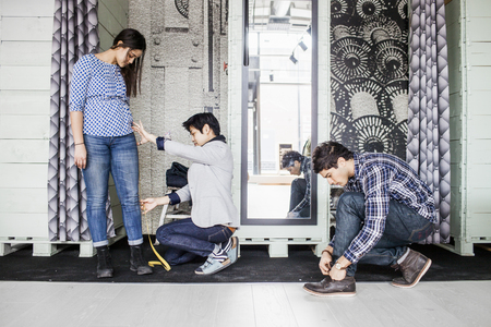 purchasers: Fashion designer taking measurement of female client while man tying shoe lace in jeans factory