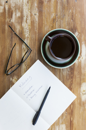 strikethrough: Directly above shot of Monday checklist with glasses and black coffee on wooden table