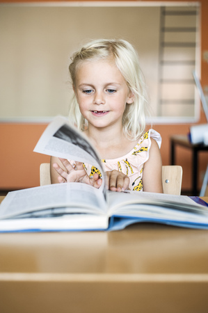 turning the page: Cute girl turning book page in classroom