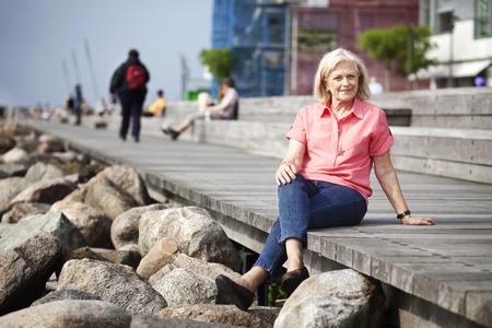 Full length portrait of happy senior woman relaxing on floorboard at seashore