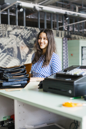 purchasers: Young female customer standing at checkout counter in jeans factory