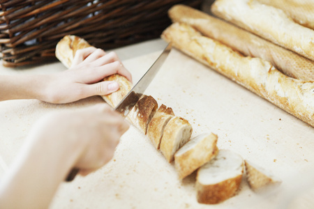 Cropped image of chefs hands cutting breadstick on table