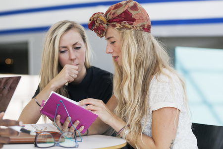 estudiantes adultos: Female friends reading notes together in college cafe