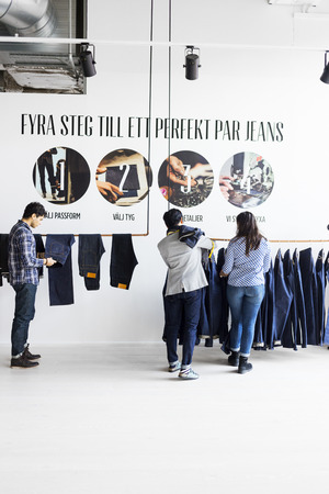 purchasers: Fashion designer and clients choosing jeans in factory