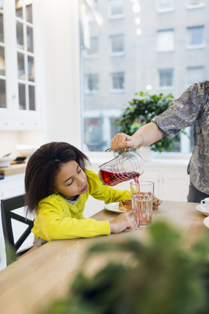 kitchen island: Mother serving glass of juice to daughter in kitchen