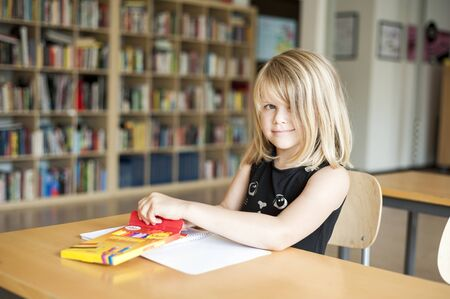 primary product: Portrait of girl coloring at desk in classroom