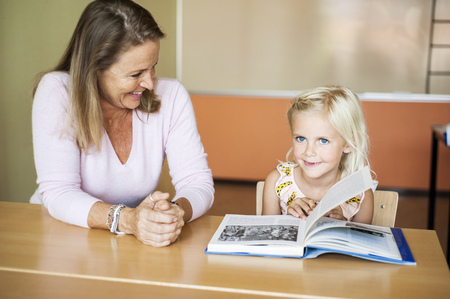turning the page: Happy teacher looking at girl turning book page in classroom