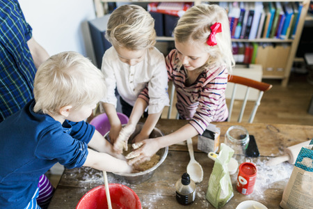 family: High angle view of children kneading dough at home