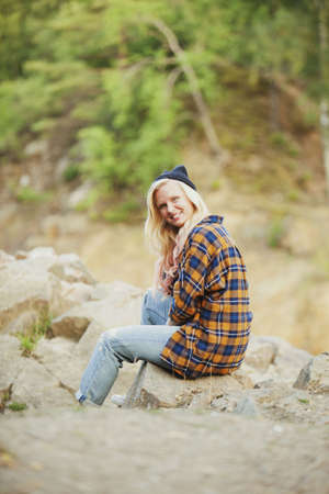 Side view portrait of happy woman sitting on rock in forest LANG_EVOIMAGES