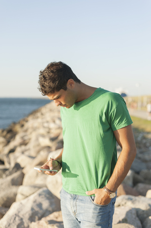 Young man using mobile phone while sitting on rocky shore