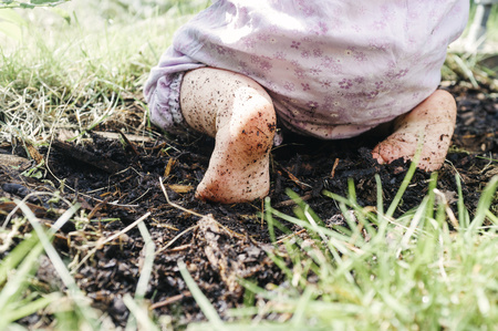 untidy: Low section of baby with dirty feet kneeling on dirt LANG_EVOIMAGES