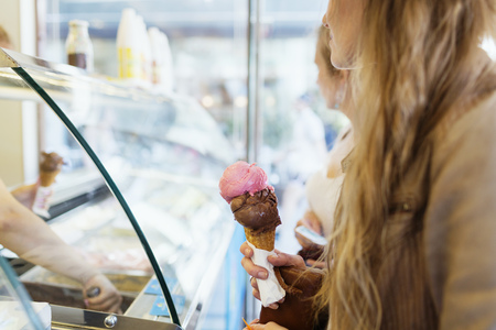 shopping binge: Midsection of woman holding ice cream cone at parlor