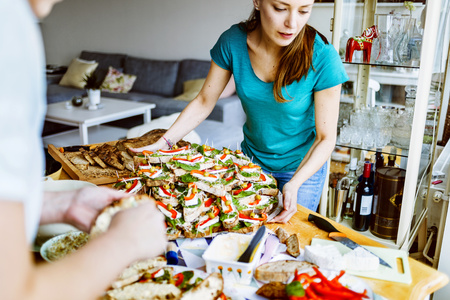 two faced: Young woman holding tray full of open faced sandwiches with friend at home