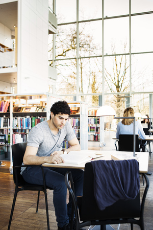 estudiantes adultos: Young man reading book at table in library