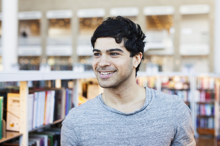 estudiantes adultos: Happy young man looking away in library LANG_EVOIMAGES