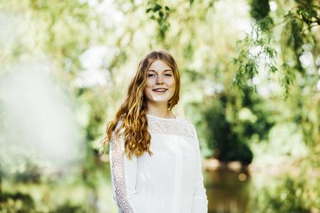 Portrait of happy female graduate at university park LANG_EVOIMAGES
