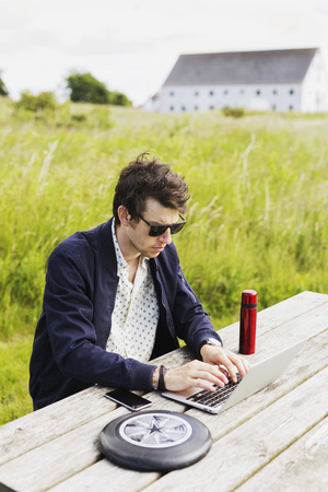 Man in sunglasses using laptop by plastic disc while sitting on grassy field LANG_EVOIMAGES