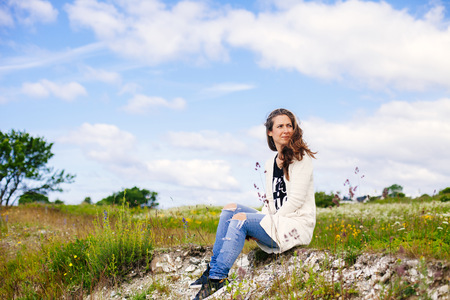 Woman looking away while sitting on field against cloudy sky