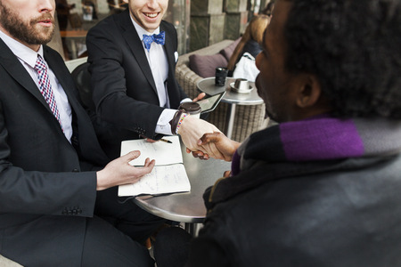 formals: Business people shaking hands while sitting with colleague at sidewalk cafe LANG_EVOIMAGES