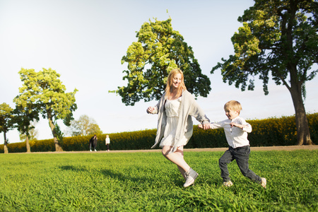 Playful mother and son running on field