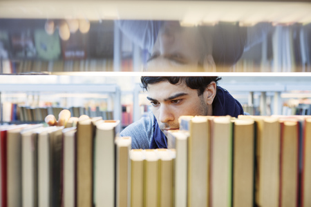 estudiantes adultos: Serious young man choosing book in library LANG_EVOIMAGES