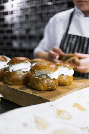 unhealthful: Midsection of chef with cream buns in kitchen