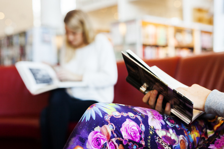 estudiantes adultos: Cropped image of woman holding book while sitting on sofa with friend in background at library LANG_EVOIMAGES