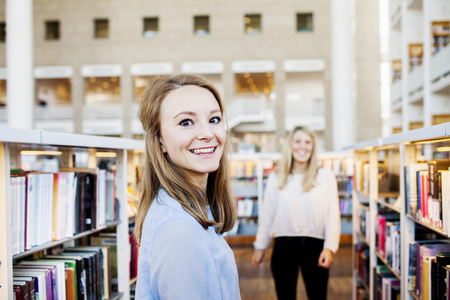 estudiantes adultos: Portrait of young student smiling while female friend standing in background in library