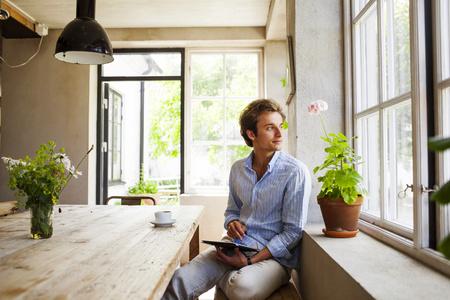 Young man using digital tablet at restaurant LANG_EVOIMAGES