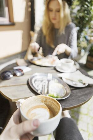 personal perspective: Cropped image of man holding coffee cup while woman eating food at sidewalk cafe
