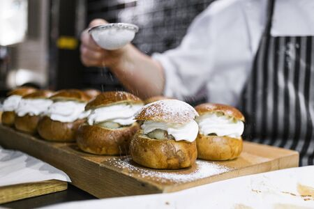 unhealthful: Cropped image of chef dusting icing sugar on cream buns in kitchen
