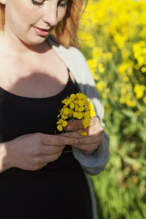 Pregnant woman looking at oilseed rape flowers on field LANG_EVOIMAGES