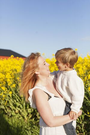 Happy woman carrying son at oilseed rape field LANG_EVOIMAGES