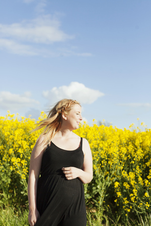 Smiling pregnant woman with eyes closed standing at oilseed rape field