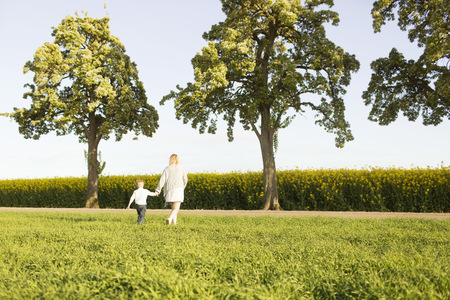 Rear view of mother and son walking on grassy field