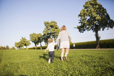 Rear view of mother and son walking on field LANG_EVOIMAGES