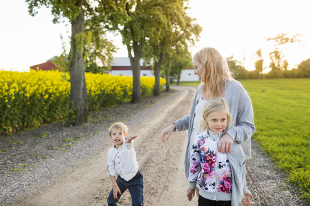 Happy family on dirt road at oilseed rape field LANG_EVOIMAGES