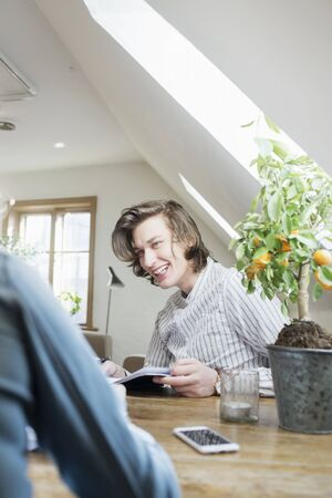 estudiantes adultos: Happy young man looking at friend while studying in restaurant