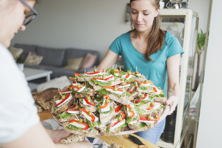 two faced: Young woman holding open faced sandwiches in tray with friend at home