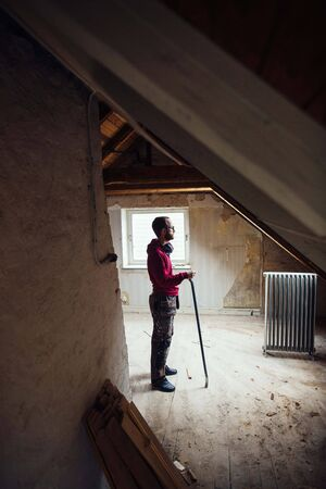 attic: Full length side view of man with work tool renovating attic