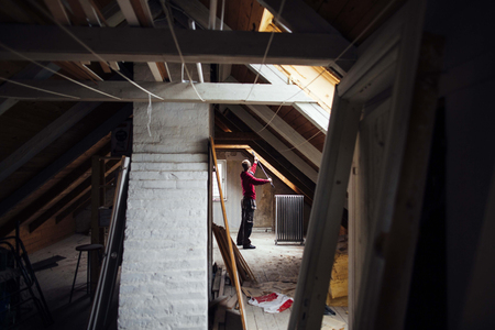 attic: Side view of man working in attic under construction