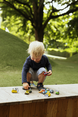 Full length of boy playing with toy cars on retailing wall in park
