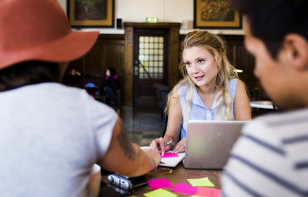 Woman talking to friends while doing freelance work at cafe table LANG_EVOIMAGES
