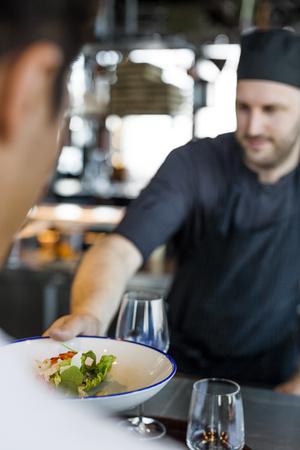 Chef serving dish to customer at Sky bar restaurant LANG_EVOIMAGES