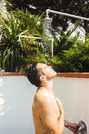 Side view of man bathing under shower in yard