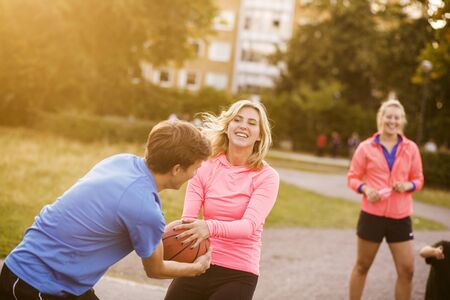 incidental people: Happy man and woman snatching basketball at park