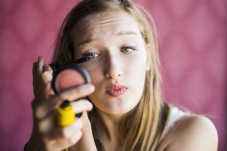 Teenage fashion model applying mascara in studio LANG_EVOIMAGES
