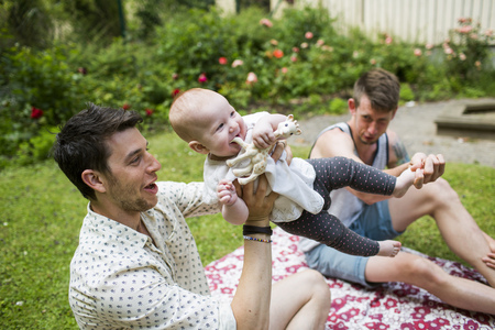 family: Happy gay men playing with baby girl at yard